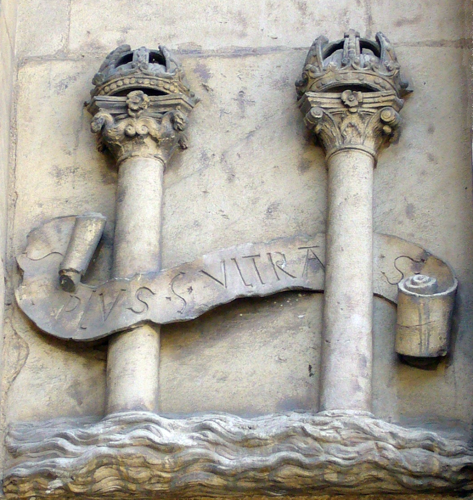 "Sculpture inspired by the coat of arms of Spain.  Photo by Ignacio Gavira at the city hall in Seville, Spain.  The inscribed motto, although in the negative form (Non Plus Ultra), was said to have been on the ancient Pillars of Hercules warning ships to travel no further.  After landing in the New World in 1492, Spain would refashion this phrase to the affirmative and seize it as their national motto.  Less than a century later, Spain would become known as the first ""empire on which the sun never sets"".  A leading theory is that this coat of arms was actually the precursor to the version of the American dollar sign that uses two vertical bars.  The motto and the pillars can be found on the modern Spanish flag."